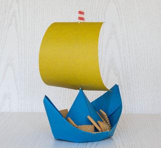 Buntes Papierschiffchen mit Segel als Schüssel