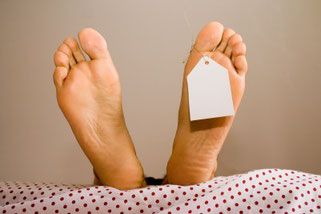 Nackte Füße auf einer Bahre mit Namensschild dran.