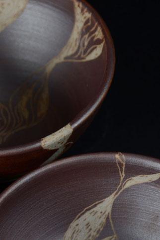 Detail Schalen, braun mit eingeritzem floralem Motiv