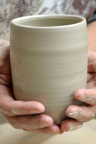 Zwei Hände halten ein frisch gedrehtes Keramikgefäß