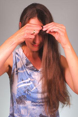 Haarsträhne vom Finger nehmen