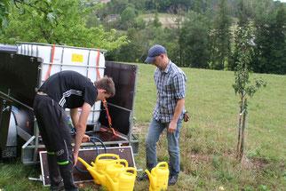 Peter Schlör (rechts) und Finn Hökel beim Gießen der neuen Obstbäume.