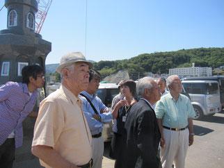 女川港の慰霊碑の前で阿部さんに説明を受ける視察メンバー
