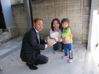 蒲生様の末娘のきずなちゃん(3歳)より直接手渡し頂く高崎理事長
