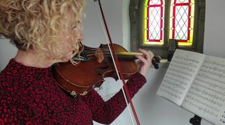 Eine Musikerin spielt Geige. Als Zeichen für die  Behanung von Musikererkrankungen (Musikermedizin)