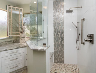 Shower with gray wall tiles. The bench and the curb are both topped with marble slab.