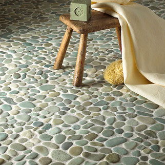 Bathroom floor with green and gold pebbles.