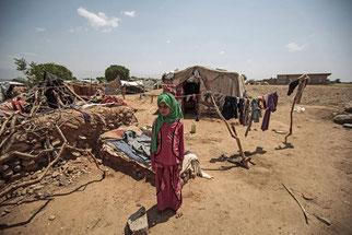 Una niña yemení desplazada internamente de pie fuera de su tienda. Foto (CC) /FAO