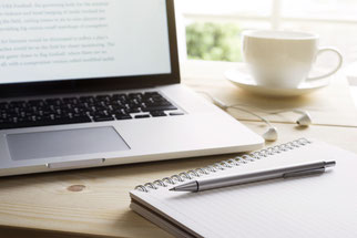 Laptop mit Notizblock und Stift