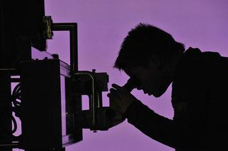 Schattenriss eines Mannes, der in ein Mikroskop blickt