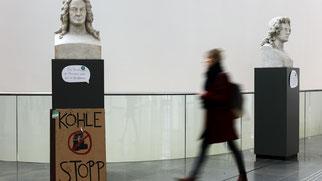 """Ein Pappschild """"Kohle Stopp"""" steht am Sockel der Büste von Gottfried Wilhelm Leibniz während der Klima-Aktionswoche im Neuen Augusteum der Uni Leipzig.   Foto: Jan Woitas"""