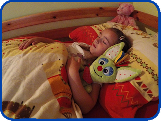 Kind schläft mit Stoffpuppe