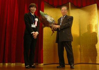 叙勲祝いの花束贈呈。石戸谷さんと横内理事長
