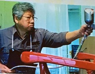 ダニエルの赤い椅子を塗装する原氏耕二氏
