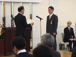 小俣一夫会長より表彰される三富啓成氏