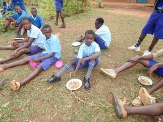 Emmanuel (Bildmitte) beim Mittagessen an der Schule (Hftc ermöglicht es ihm, dass er über Mittag an der Schule essen kann)