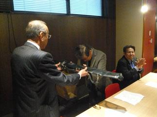 歴代会長に継承される木刀が西村会長から稲留先輩へ授与される。