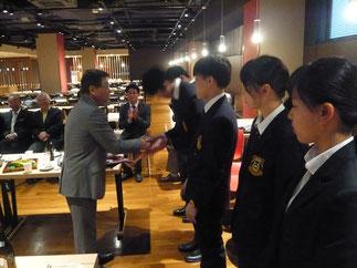 稲留新会長から新入部員へ入部の証である手拭が贈呈される。