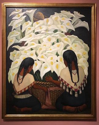 Een enorme bos Callas lelies in een mand met daarvoor twee geknielde mexicaanse vrouwen.