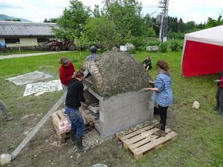 Isolierschicht wird angebracht - Lehmbackofen fasst fertig