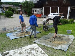 Lehmisolierung wird gemischt - Workshop-Teilnehmer des Lehofenkurses