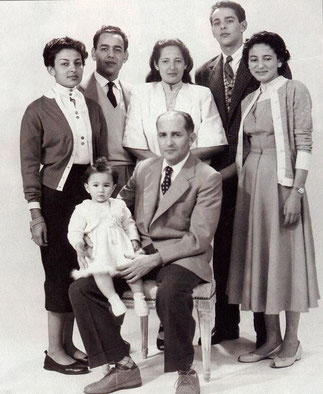 Madagascar 1954. Le roi Mohammed V assis, entouré de Lalla Aïcha,Moulay Hassan,Lalla Malika,Moulay Abdullah et Lalla Nezha. Sur ses genoux, Lalla Amina.