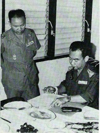 1970. Le général Vang Pao debout et le Prince Ministre Sisouk Na Champassak étudiant un plan de riposte.