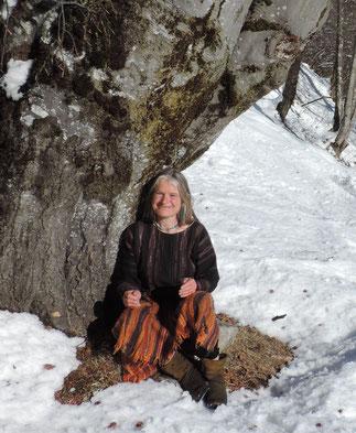 Annett in der Wintersonne bei einem mächtigen Baum sitzend
