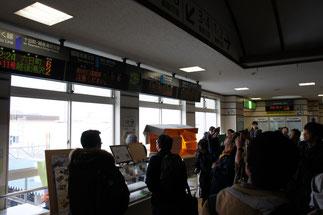 電光掲示板をカメラに収める、多くの鉄道ファン