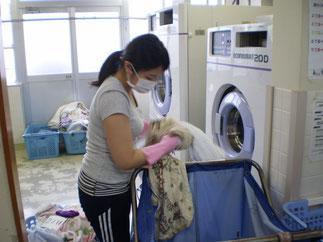 各ユニットから回収した洗濯物を機械にかけていきます
