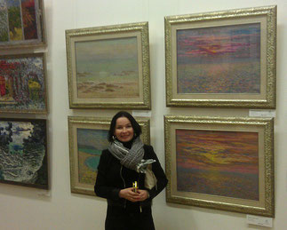 Художник Мария Богачева на фоне своих работ.