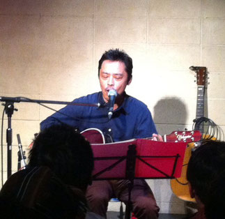 「あさがやドラム」オーナーの小川敬一さんがギターの弾き語りをしている場面