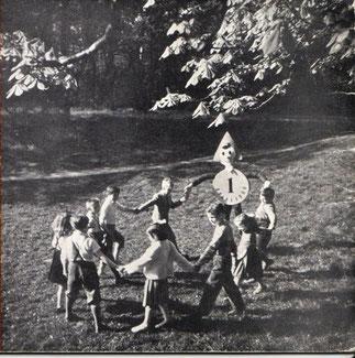 Sparefroh tanzt mit Kindern. Fotografie um 1957.