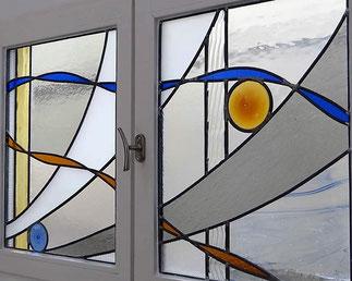 Fenêtre d'une cuisine doublé d'un vitrail abstrait composé de verres imprimés, colorés (jaune, bleu,gris,orange), et de deux cives (jaune, bleu). Création réalisée par Marion Rusconi  à l'atelier le chant du diamant (Lyon 69004).