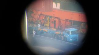 望遠鏡からの画像。ちょうどトレーラーに40フィートコンテナを積むところ。作業員の様子が丸見え。