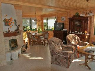 Helles und lichtdurchflutetes Wohnzimmer mit Kamin - Einfamilienhaus  - Blockhaus Immobilie  - ©Blockhaus-Profi