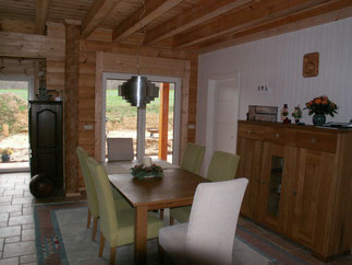 Der geräumige Essbereich mit Ausgang zur Terrasse -  Diffusionsoffene Lasuren unterstreichen das natürliche Aussehen und  die Farbe des Holzes - © Blockhaus-Profi
