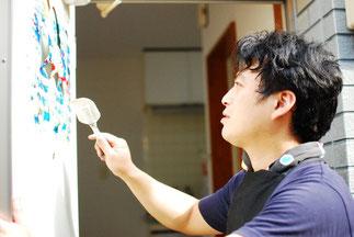 アートルームの壁に作品を描く門田氏