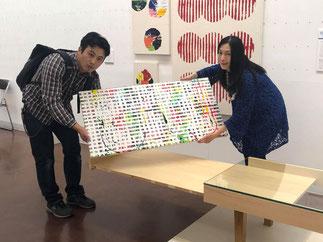 テーブル一体型の門田さんの絵画をテーブルから取り出す門田氏とこの作品をコレクションした菊池