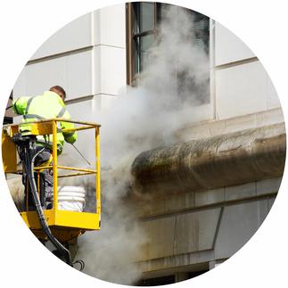 Fassadenreinigung, Mann reinigt Fassade mit Dampfstrahler