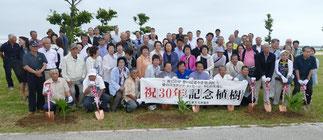 愛知県田原市から87人もの訪問団が来訪し記念植樹を行った=28日午後、南ぬ浜町ビーチ