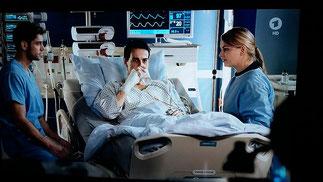Arzt sitzt in der TV Serie bei der Medikamentengabe am Patientenbett und vermittelt so Sicherkeit. Ein Patiententraum!