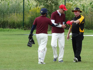 Alex Mackay (r) on international cricket umpiring duty in Warsaw 2016