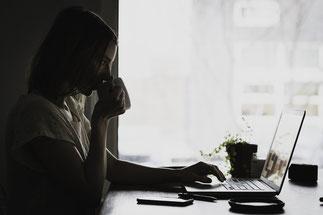 femme qui boit un café devant son ordinateur