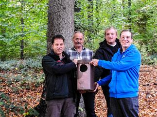 Holger Puls, Martin Welsch, Daniel Spönemann und Dr. Nick Büscher mit einem Waldkauzkasten am Bartelsweg. - Foto: Kathy Büscher