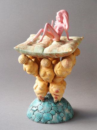 Turmförmige Skulptur auf halbkugeligem Sockel mit Muschelmuster, darauf eine Gruppe Venus von Willendorf-Figuren, darauf ein bedrucktes Kissen mit einer sitzenden Barbie