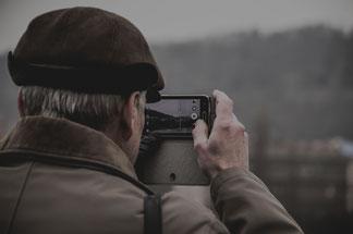 Rentner fotografiert mit Handy