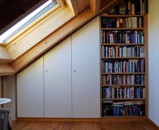Einbauschrank mit Regalteil in der Dachschräge. Weiße Türen und ein offenes Bücherregal