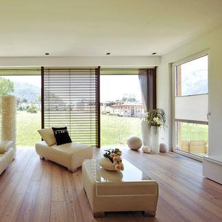 Geräumiges Wohnzimmer mit Raffstoren auf den Glasfenstern und Blick auf den Garten