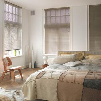 Innenjalousien in einem Schlafzimmer mit großem Doppelbett